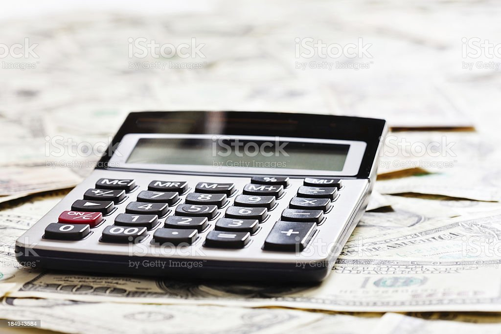 Calculator against a background of multiple out-of-focus  US dollars royalty-free stock photo