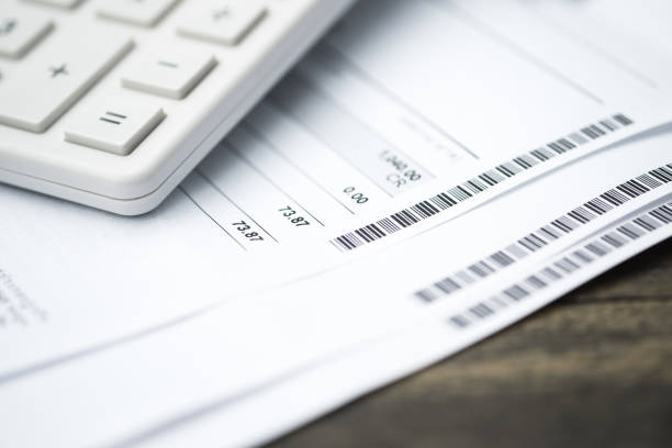 Calculator and bill payment as background. Income, expenses, tax, financial data. stock photo