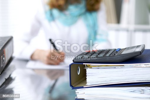 istock Calculator and binders with papers are waiting to be processed by businesswoman or secretary back in blur. Internal Audit and tax concept 868533340