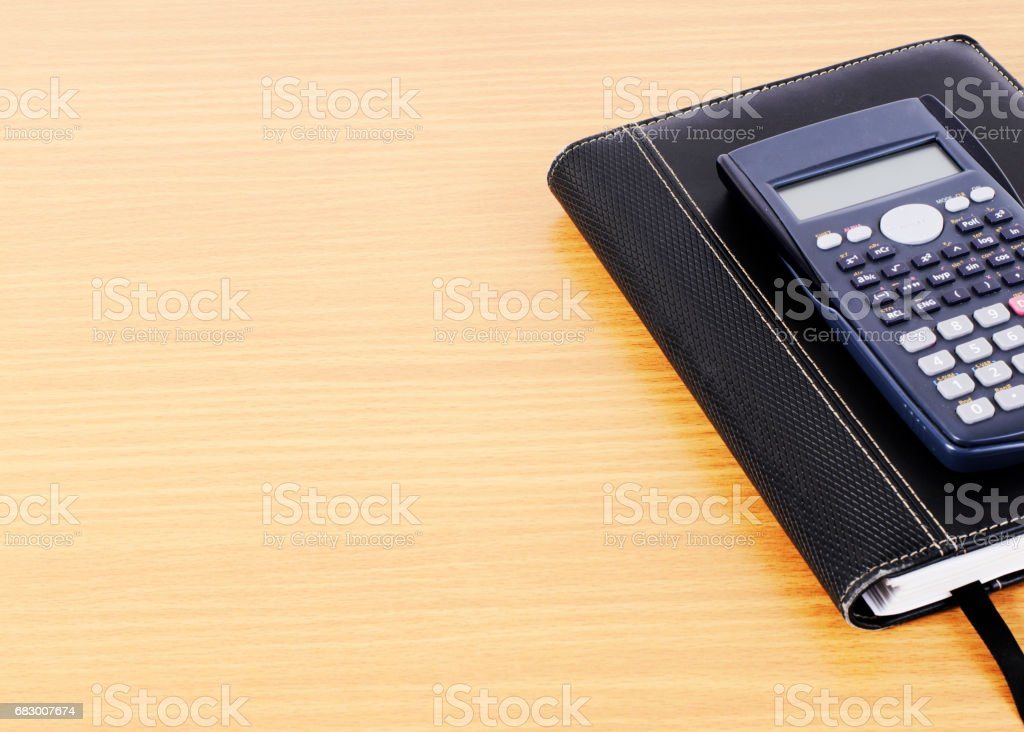 Calculator and Business book on wooden desk background royalty-free stock photo