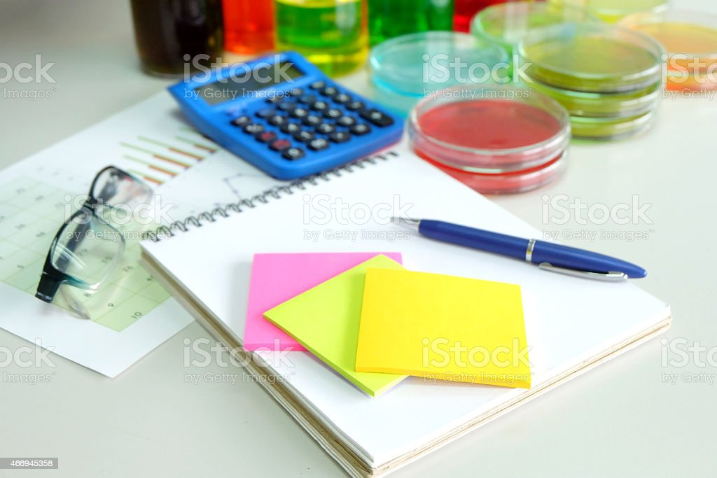 calculator and chart with colorful fluid in glassware stock photo