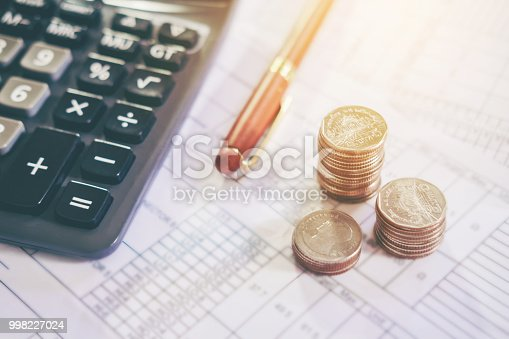 Calculator and coin on the business paper. Report chart