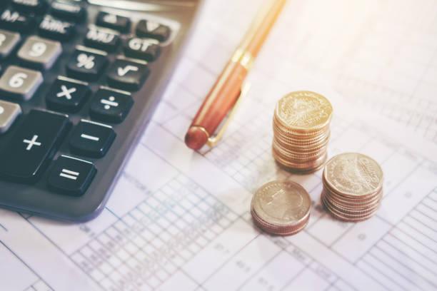 Calculadora y la moneda en el papel de la empresa. Tabla de informe - foto de stock