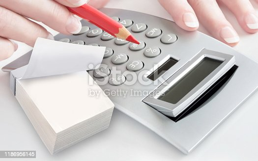 1170746979istockphoto Calculator and female hand with red pen 1186956145