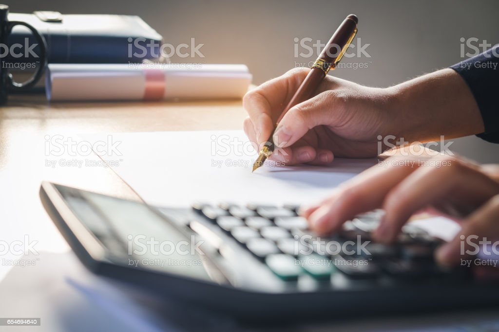 calculator and Financial data analyzing hand writing and counting in office on wood desk stock photo