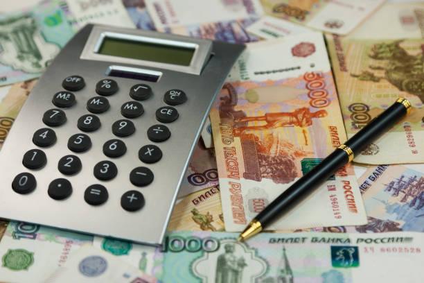 계산기와 돈을 루블의 배경에 거짓말. 아이디어와 비즈니스의 개념 - 러시아 루블 뉴스 사진 이미지
