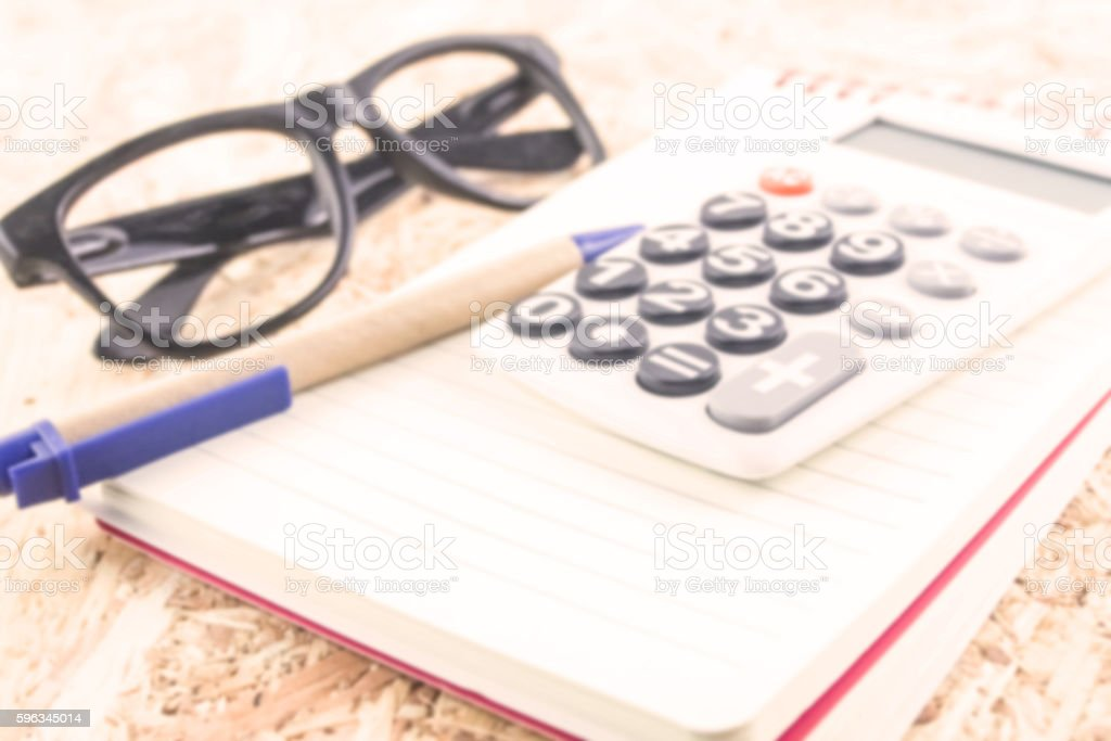 calculator and notebook pen eyeglasses on wood table vintage tone royalty-free stock photo