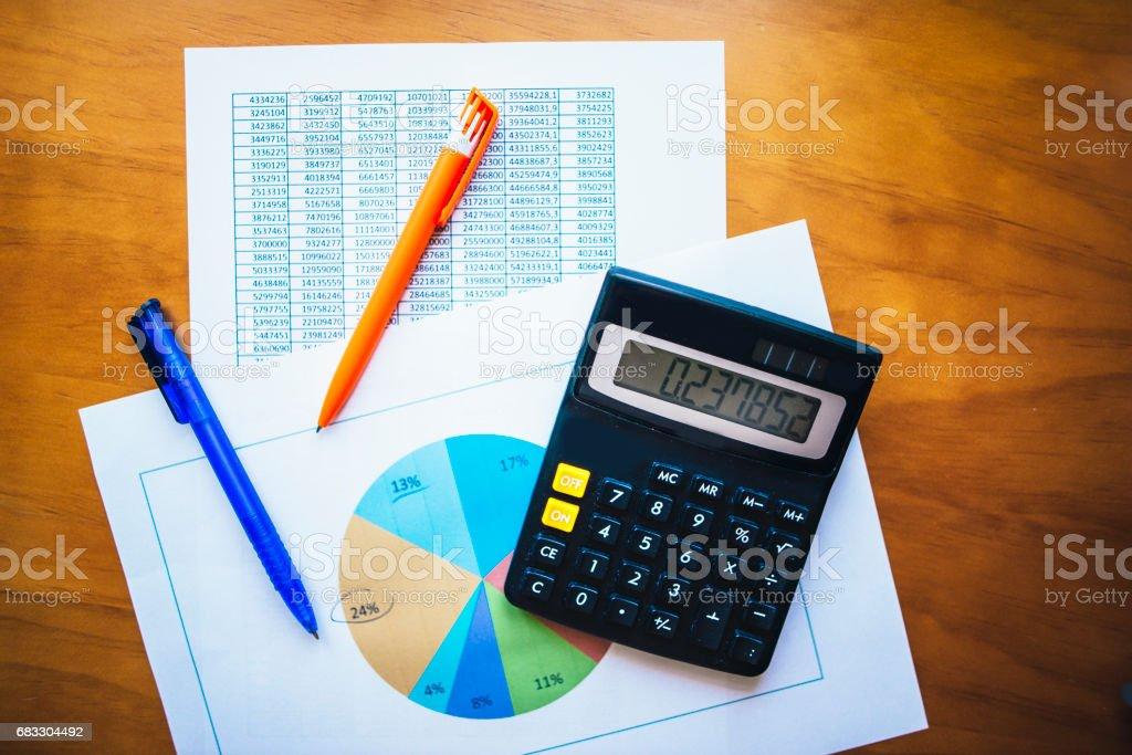 Calculator and paper sheets with data royaltyfri bildbanksbilder