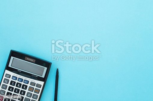 Calculator and pen on a blue background. Top view.