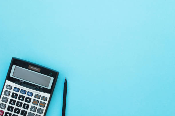 Calculator and pen on a blue background. Calculator and pen on a blue background. Top view. calculator stock pictures, royalty-free photos & images