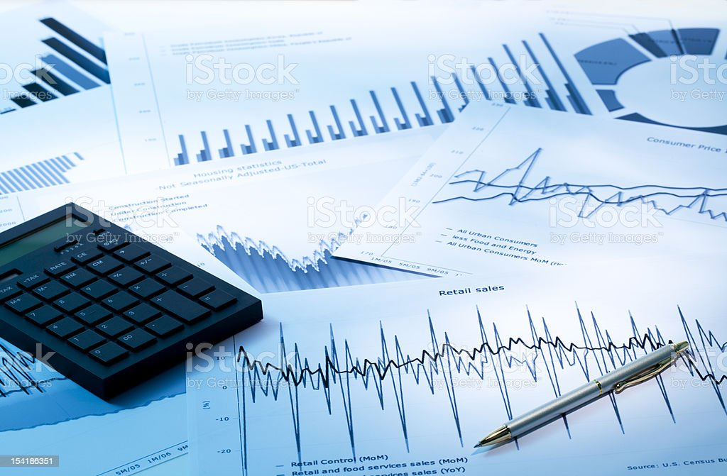 Calculator and pen on a pile of many graphs and charts stock photo