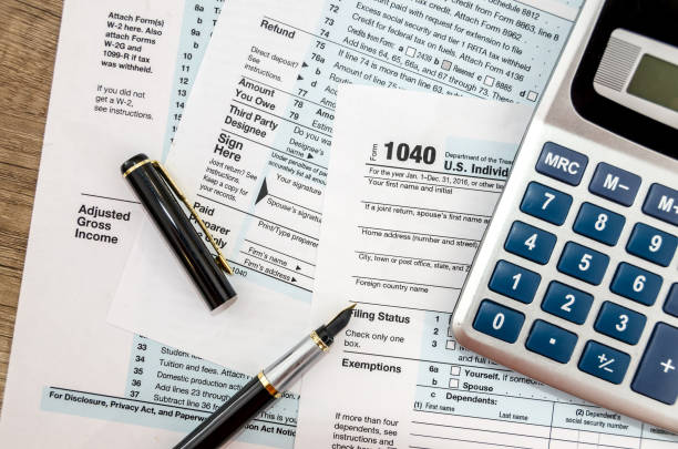 Calculator and pen with 1040 tax form Calculator and pen with 1040 tax form income tax stock pictures, royalty-free photos & images