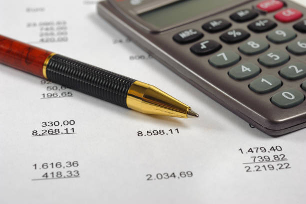 calculator and pencil laying on financial business account stock photo