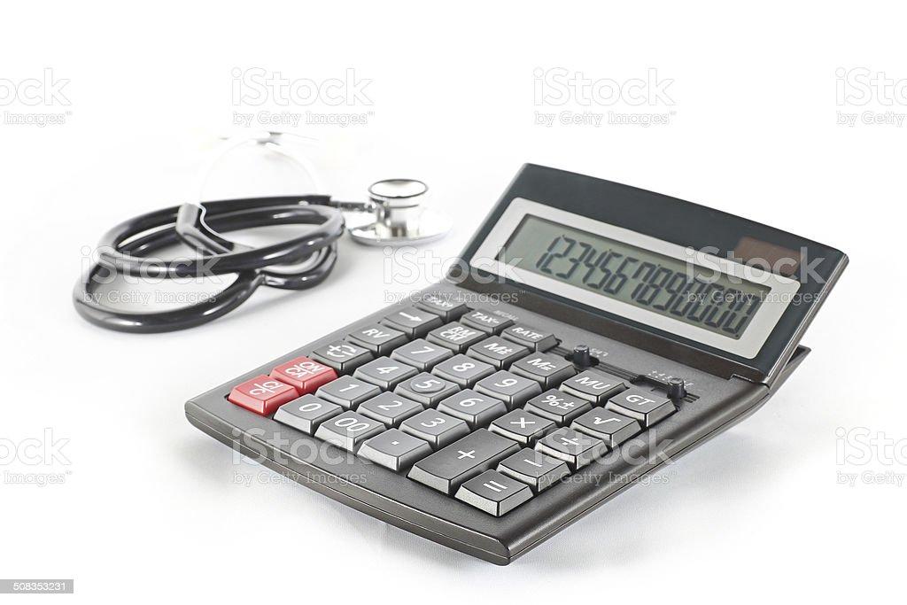 Calculator and stethoscope stock photo