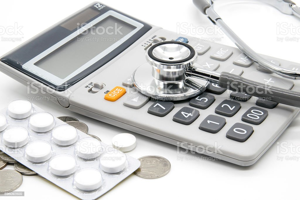 Calculator and stethoscopes on white background royalty-free stock photo