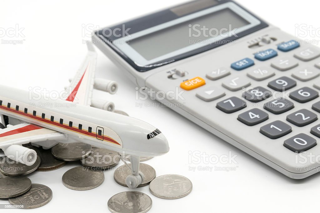 Calculator and toy plane on white background stock photo