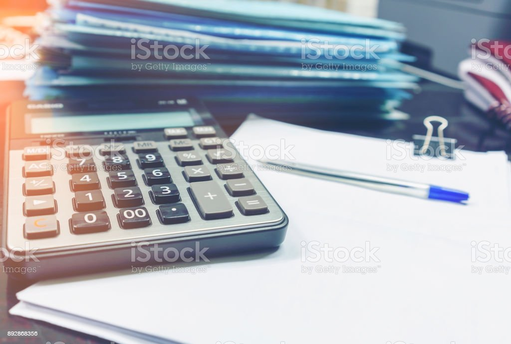 Calculator , ball pen and pile of work on the table in the office stock photo