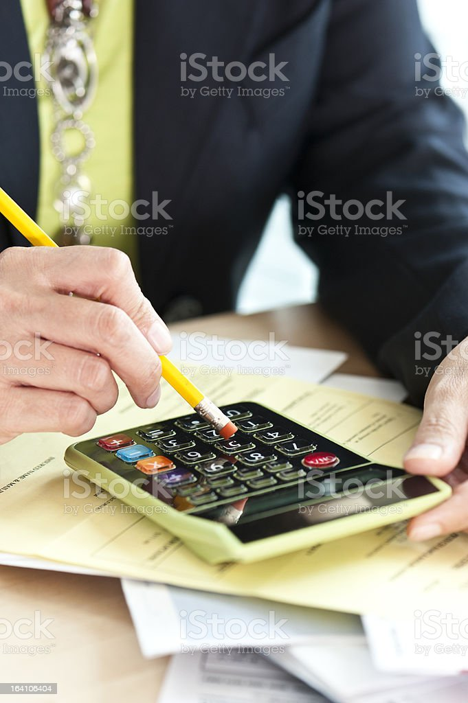 female hands using a calculator on top of household bills