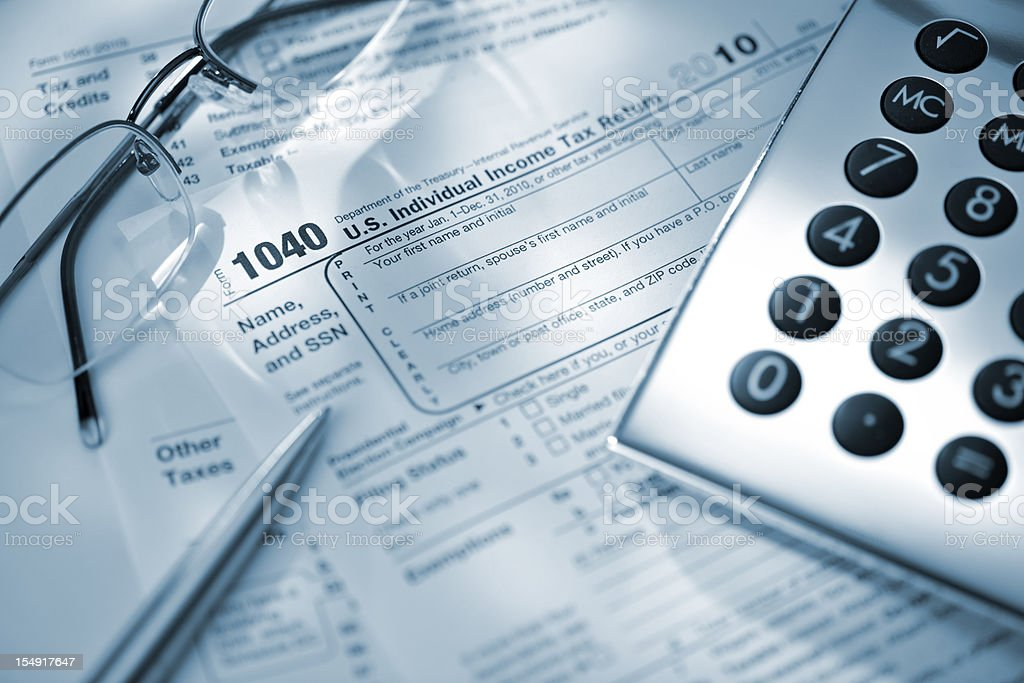 calculator glasses and pen on US tax return form royalty-free stock photo