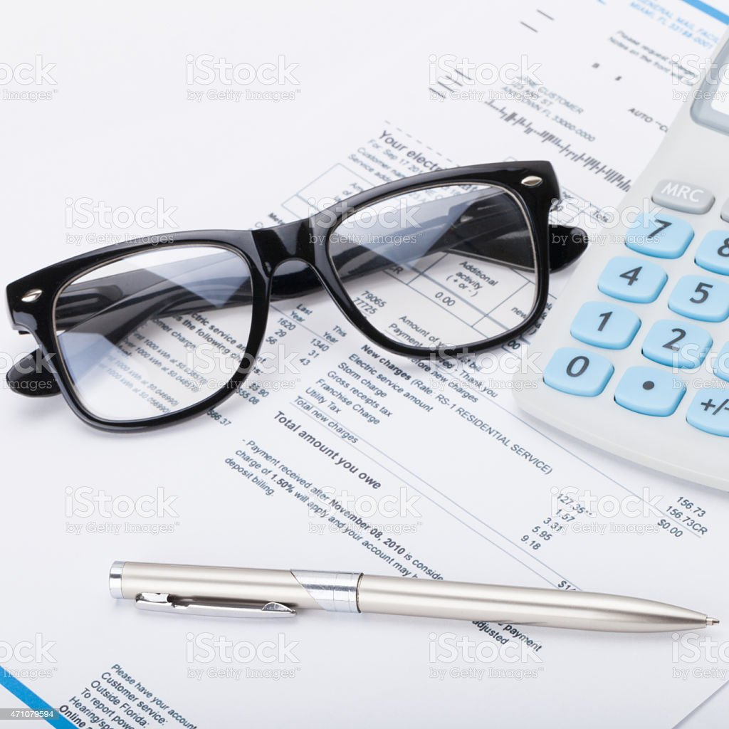 Calculator, glasses and utility bill under it stock photo