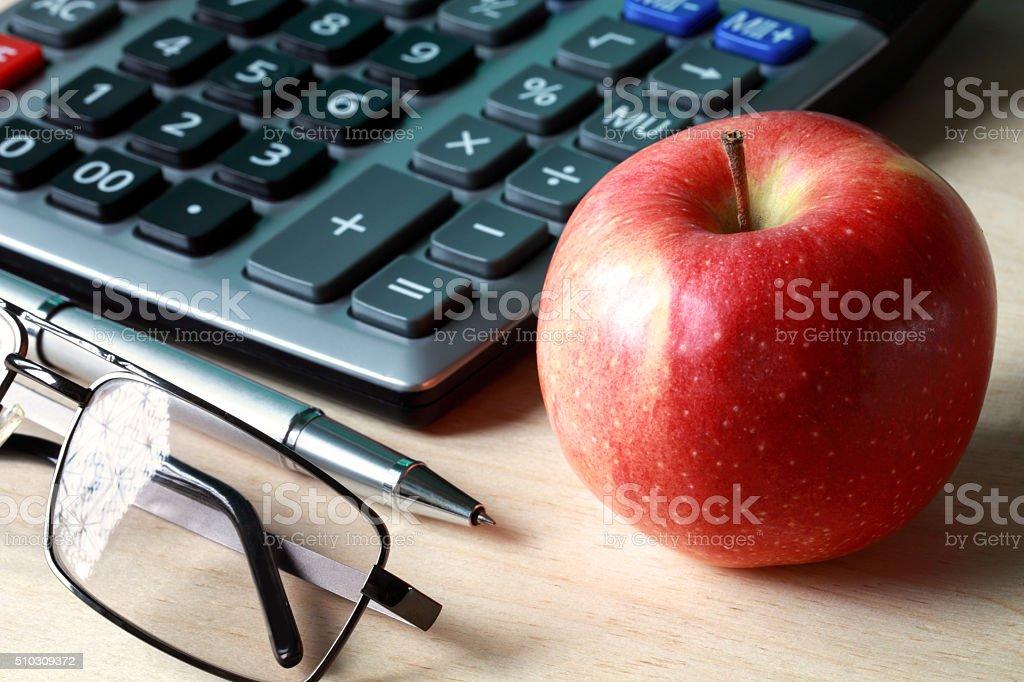 Calculator, glasses, pen and apple stock photo