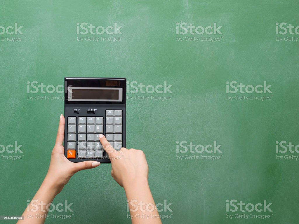Calculator in human hand on blackboard for education costs stock photo