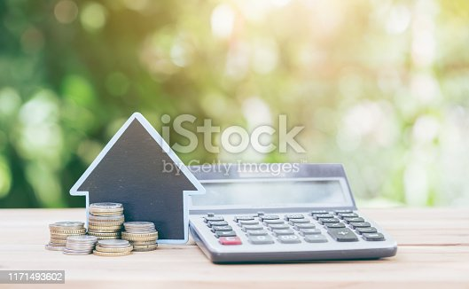istock Calculator is placed on the wood and house placed on coins. Imagine calculating to buy a home. 1171493602