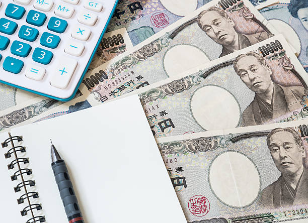 Calculator, notebook and pencil on Japanese yen currency stock photo