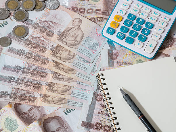 Calculator, notebook and pencil on Thai baht currency stock photo