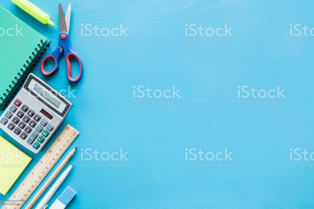Calculator, notebook, pen, scissors and other office or school supplies on a table. Empty place for text on the blue background. Education concept. Flat lay. stock photo
