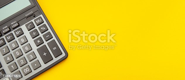 Calculator on a stretched yellow background with space for text, business and finance concept