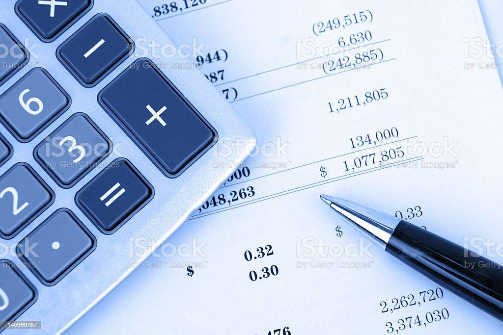 Calculator on balance sheet with blue overlay royalty-free stock photo