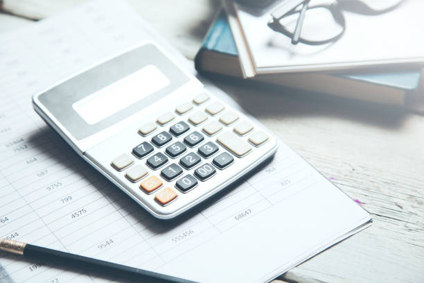calculator on document on wooden desk stock photo