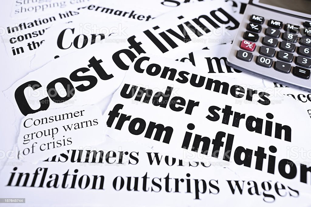 Calculator on newspaper headlines about cost of living and inflation royalty-free stock photo