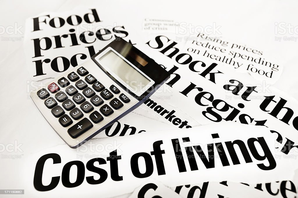 Calculator on newspaper headlines about high cost of living royalty-free stock photo