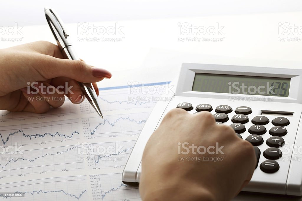 calculator on on white paper with financial data and chart royalty-free stock photo