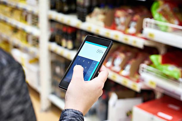 Calculator on smartphone screen in hand of women customers stock photo