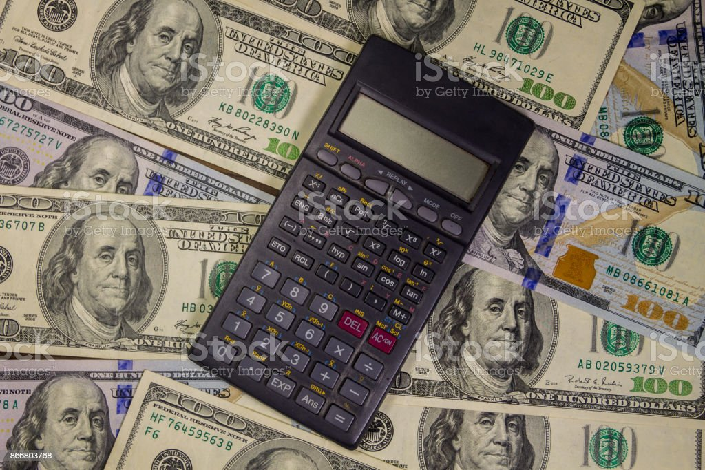 Calculator on the American one hundred dollar bills background stock photo