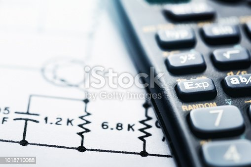 Cropped look at a calculator sitting on top of a complex technical drawing or diagram.