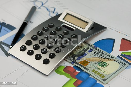 851244800istockphoto Calculator, one hundred dollars and a pen lying on the diagrams. 870441686