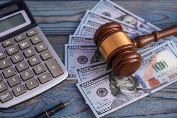 kalkulator, pena, palu hakim, uang kertas dolar amerika di latar belakang - best tax attorney potret stok, foto, & gambar bebas royalti