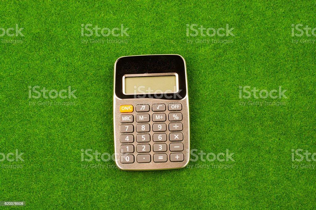 Calculator placed in green grass zbiór zdjęć royalty-free