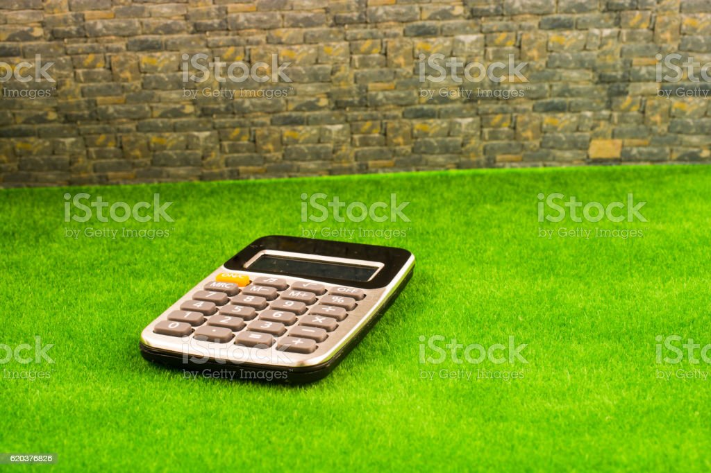 Calculator placed in green grass zbiór zdjęć royalty-free