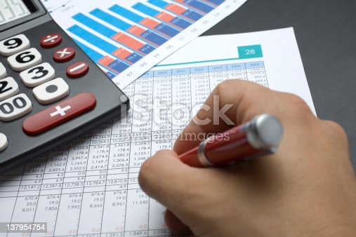 Close up of a calculator, spreadsheet, data and pen on a table.
