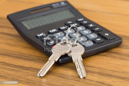 Calculator with a house key. Wooden table background. Housing loans, mortgages and real estate concept.