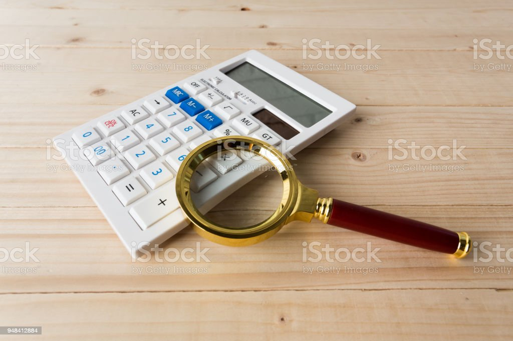 Calculator with a magnifying glass stock photo
