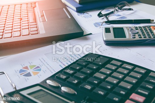 istock Calculator with business graphs and charts report on tabble, calculator on desk of financial planing. Financial concepts. 821678930
