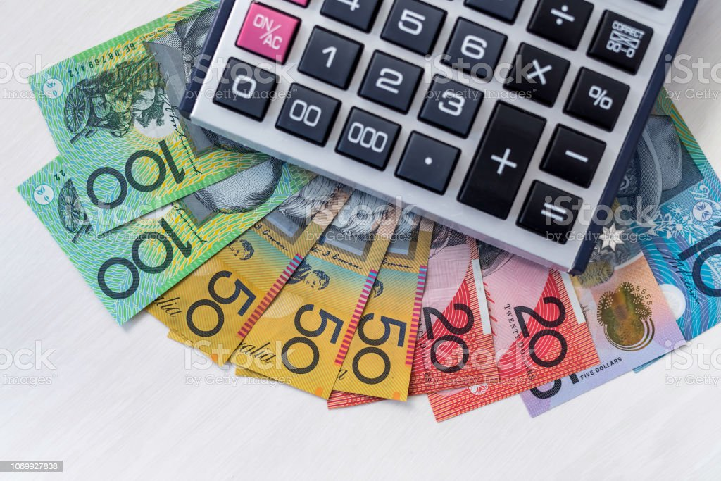 Calculator with colorful australian dollars on wooden table stock photo