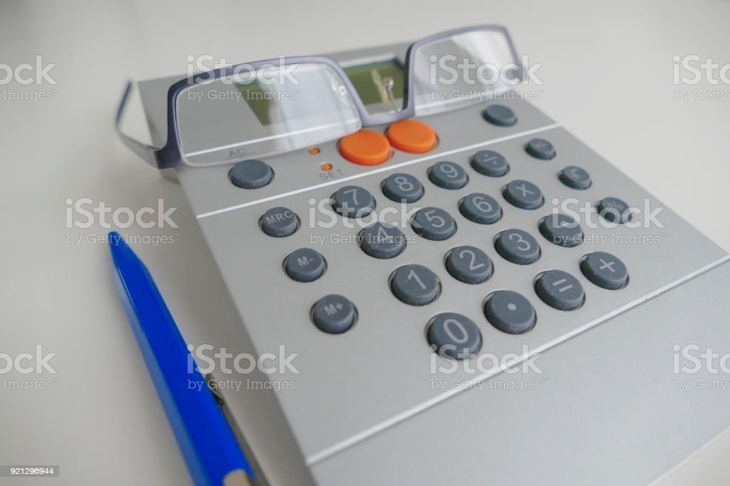 Calculator with eyeglasses and a blue ballpoint pen on white table stock photo