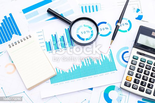 Calculator with Magnifying and Pen on Business Graphs finance document.